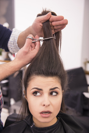 Female client in hairdressing salon scared about cutting. photo