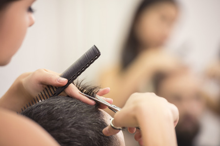 young man short hair: Close-up hairdresser with scissors and comb. Blurred background. Stock Photo