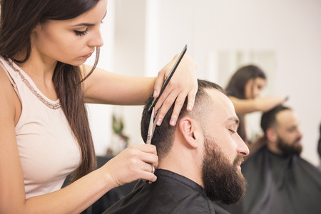 Female hairdresser is cutting hair of man client.