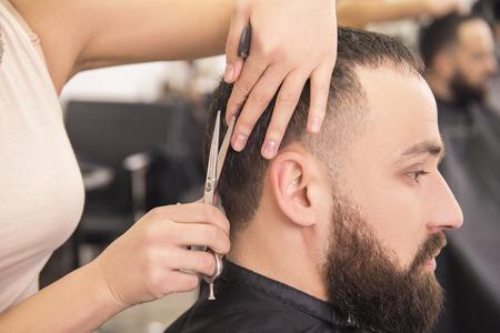 hombre con barba: Primer plano peluquería femenina del corte del pelo del hombre cliente.