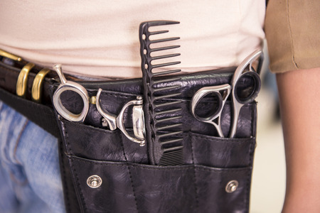 haircutting: Close-up of tools of a professional hairdresser neatly stored in a leather belt.
