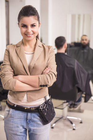 Young beautiful hairdresser in leather belt with tools  in salon. Client on the background. photo