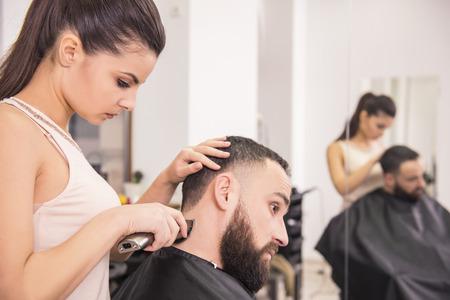 Friseur schneidet Haare mit Haarschneidemaschine auf der Rückseite des Kopfes in Friseursalon