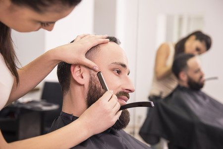 hairdresser: Hairdresser shaving an old-fashioned razor of satisfied client in professional hairdressing salon.