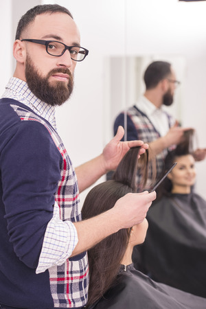 Handsome hairdresser making a haircut for a beautiful brunette girl and looking at camera. photo