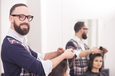 Male hairdresser making a haircut for a beautiful brunette girl in professional hairdressing salon. photo