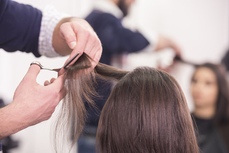 Close-up hairdresser cutting hair a woman in hairdresser salon. 스톡 콘텐츠