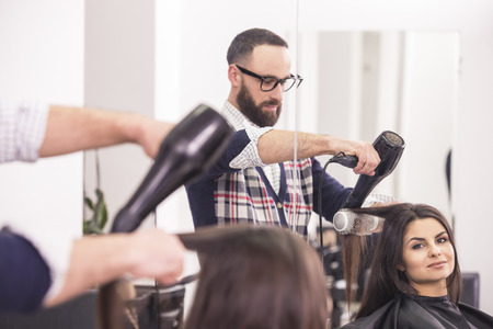blow dry: Hairdresser blow dry beautiful  woman hair in hairdressing salon. Stock Photo
