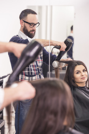 Hairdresser blow dry beautiful  woman hair in hairdressing salon. photo