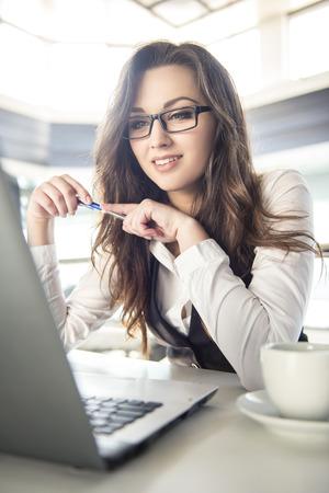 Jonge zaken vrouw die werkt voor een laptop met een kopje koffie in een modern kantoor.