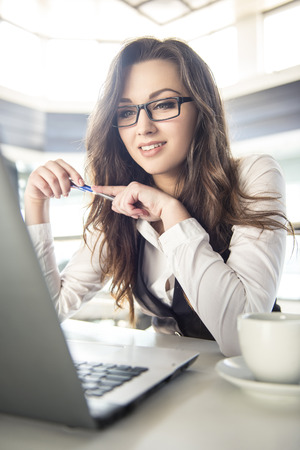 Young business woman working for a laptop with a cup of coffee in a modern office.