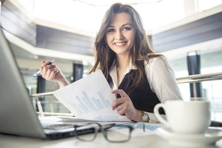 work. office: Younge beautiful business woman working with documents in the office Stock Photo