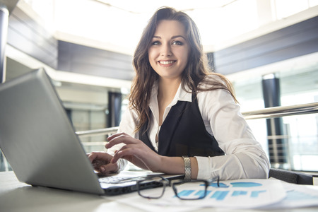 Jeune femme d'affaires travaillant pour un ordinateur portable dans un bureau moderne.