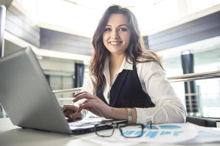 Mujer de negocios joven que trabaja para un ordenador portátil en una oficina moderna. Foto de archivo - 37781087