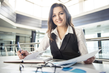 Younge beautiful business woman working with documents in the office Foto de archivo