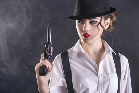 dangerous: Beautiful and dangerous. Young female gangster holding the gun. isolated on dark background.