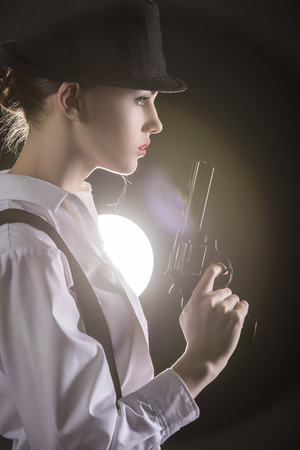 Beautiful and dangerous. Young female gangster holding the gun. isolated on dark background. photo