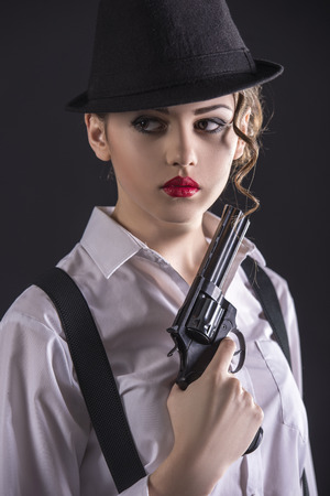 female assassin: Beautiful and dangerous. Young female gangster holding the gun. isolated on dark background.