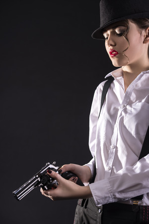 gangster background: Beautiful and dangerous. Young female gangster holding the gun. isolated on dark background.