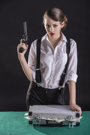 Beautiful and dangerous. Young female gangster holding the gun. isolated on dark background. On the green table a bag of cash. photo