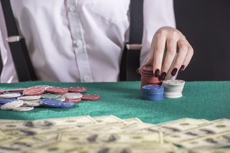 Beautiful and dangerous. Young female gangster play poker. isolated on dark background. photo