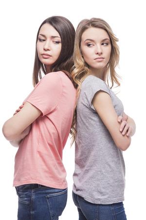 woman angry: Dos mujeres de pie espalda con espalda sin hablar el uno al otro en el fondo blanco.