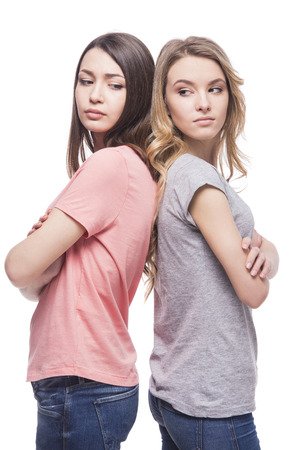 woman back: Two women standing back to back not speaking  to each other on white background.
