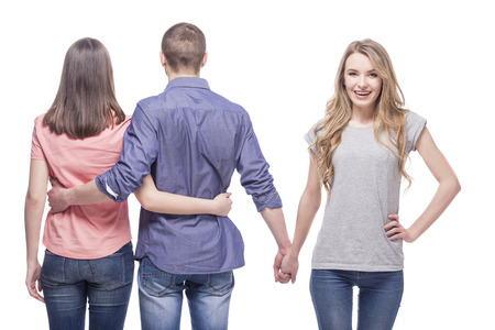 Love triangle. Handsome man embrace his girlfriend while holding hands with another girl. isolated on white background. photo