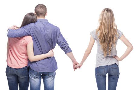 novio: Tri�ngulo de amor. Hermoso hombre abraza a su novia mientras mantiene las manos con otra chica. aislado en el fondo blanco. Foto de archivo