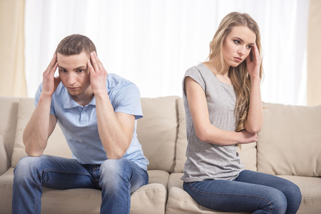 relationship difficulties: Relationship difficulties. Depressed young man and woman sitting close to each other on the couch and holding head in hands. Stock Photo