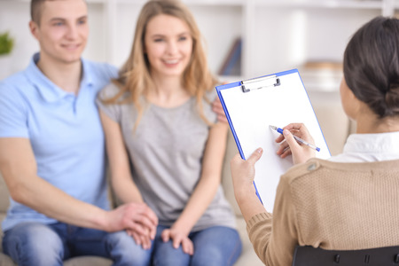 marriage counseling: Young happy couple after therapy session with family psychologist. Focus on psychologist. Stock Photo