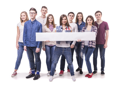 woman holding sign: Happy young students standing and smiling. White table with empty space for the text. Isolated on white background.