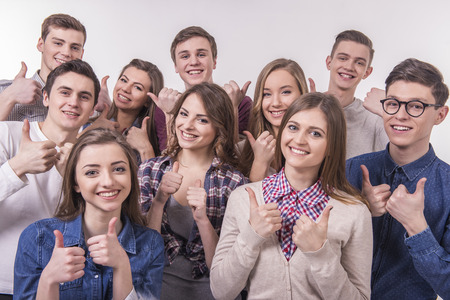 business fashion: Happy smiling young group of friends with thumbs up. isolated over a grey background. Stock Photo