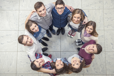 together: Top view of young people  together in a circle and looking at camera.