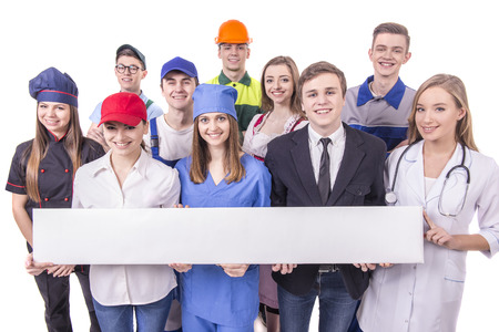 Young group of industrial workers. Isolated on white background. White table with empty space for the text.