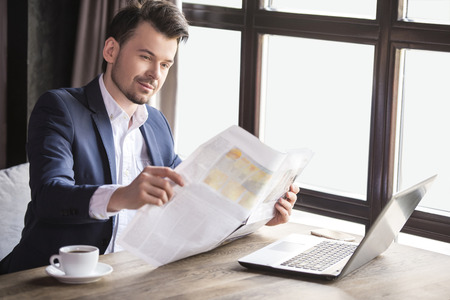 Handsome young businessman reading newspaper with cup of coffee in restaurant.