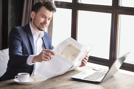 personas leyendo: Peri�dico joven apuesto hombre de negocios la lectura con la taza de caf� en el restaurante.