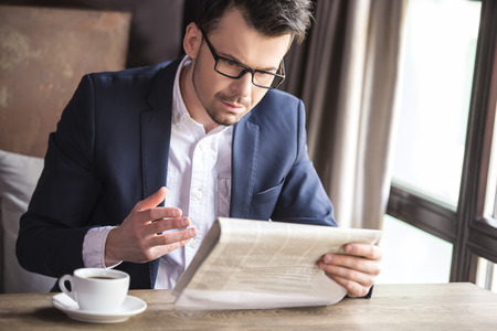 Handsome young businessman reading newspaper with cup of coffee in restaurant. photo