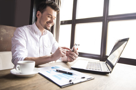 writing: Handsome businessman writing massages with cup of coffee in restaurant. Stock Photo