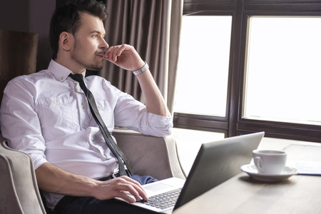 mecanografía: Vista lateral. Hombre de negocios joven hermoso que trabaja en la computadora portátil en el restaurante.