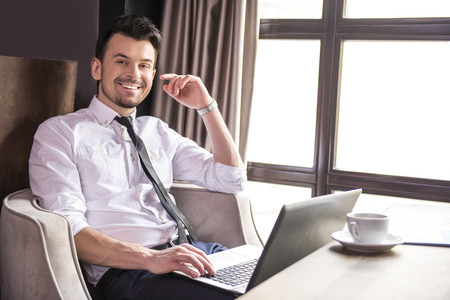 Side view. Handsome young businessman working at laptop in restaurant and looking at camera.