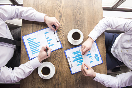 men working: Close-up. Top view. Businessman analyzing graphs with cup of coffee in restaurant. Stock Photo