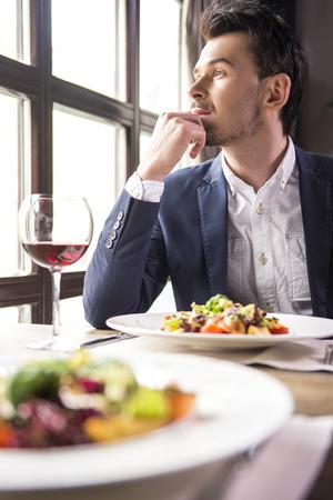 almuerzo: hombre de negocios joven guapo comer durante un almuerzo de negocios en el restaurante.