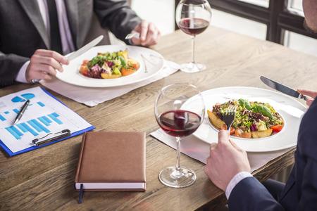 to lunch: Acercamiento. Vista lateral. Los empresarios de la alimentaci�n durante un almuerzo de negocios en el restaurante.
