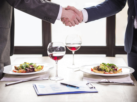 Two businessmen shaking hands during a business lunch. Business meeting.