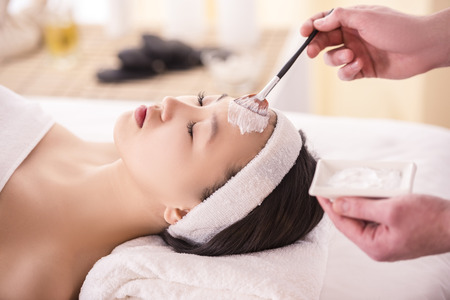 Spa therapy for young asian woman receiving facial mask at beauty salon.