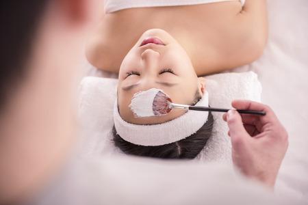 facial: Spa therapy for young asian woman receiving facial mask at beauty salon.