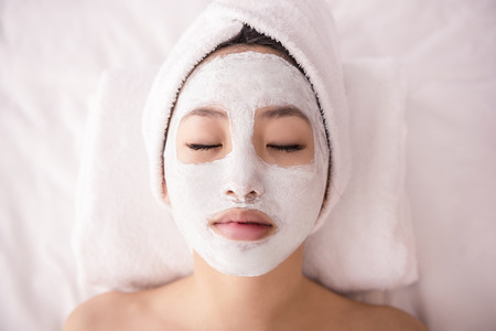 closed: Spa therapy for young asian woman receiving facial mask at beauty salon.