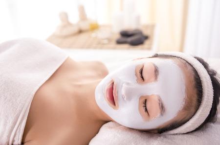 masajes faciales: Terapia de Spa para la mujer joven asiática que recibe la máscara facial en el salón de belleza.