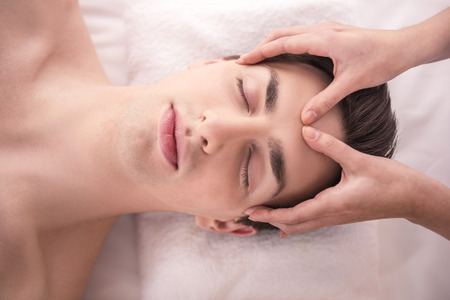male facial: Face Massage. Close-up of a Young Male Getting Spa Treatment. Stock Photo